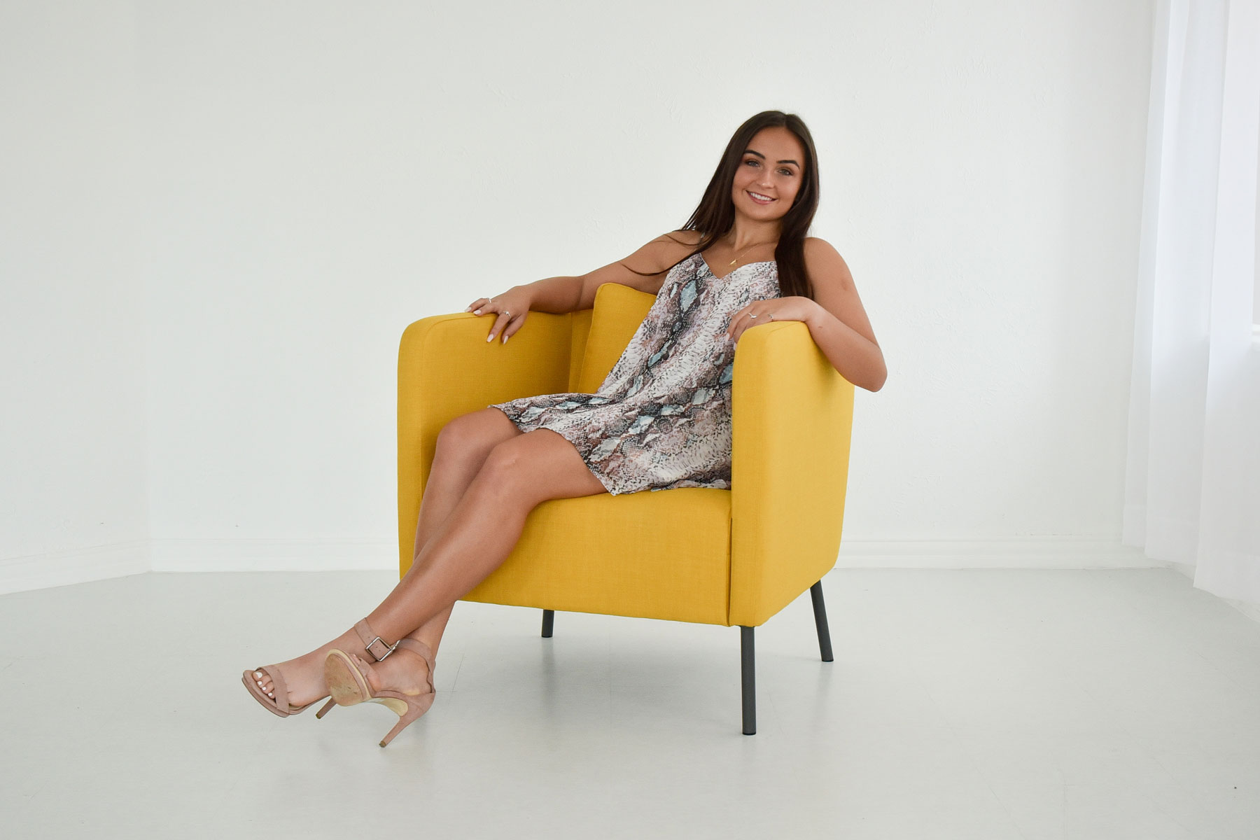 Woman Posing with Yellow Chair at Sun Catcher Studio
